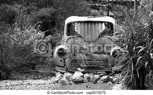 A Black And White Image Of An Old Rusted Morris Minor Car In Garden