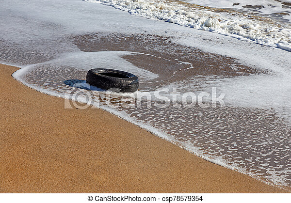 Old car tires on the beach, Water and sea coast pollution car tires on sand beach, An image of an old car tire ingrown into the sand. Old car tires with seaweed stuck on. - csp78579354