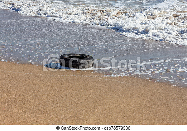 Old car tires on the beach, Water and sea coast pollution car tires on sand beach, An image of an old car tire ingrown into the sand. Old car tires with seaweed stuck on. - csp78579336
