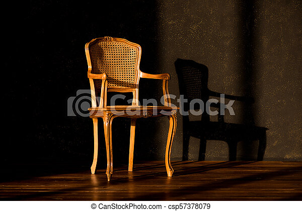 old chair on a black wall background. - csp57378079