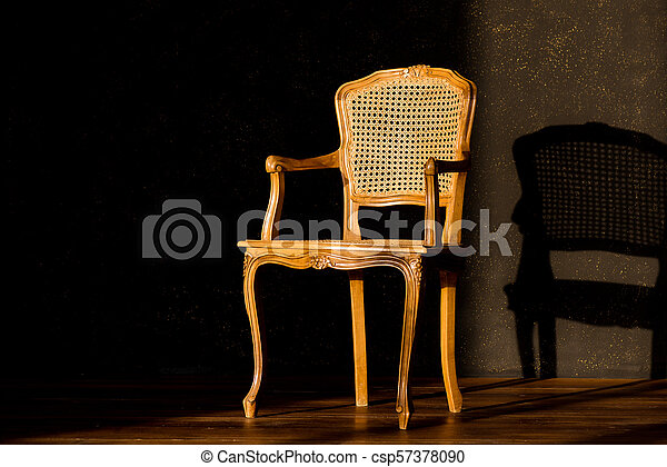 old chair on a black wall background. - csp57378090