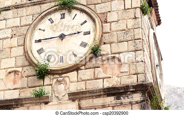 Old clock on a stone wall inside the town of Kotor - csp20392900
