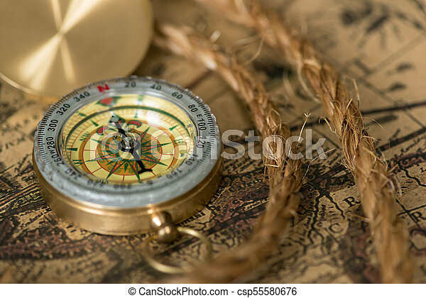 Old compass on vintage map with rope - csp55580676
