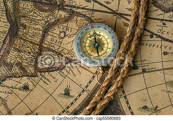 Old compass on vintage map with rope - csp55580683