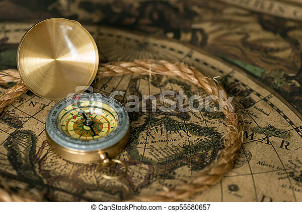 Old compass on vintage map with rope - csp55580657