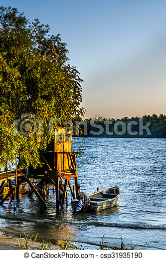 Old dock and the boat on the lake. Rustic landscape with wooden pier in the summer sunset - csp31935190