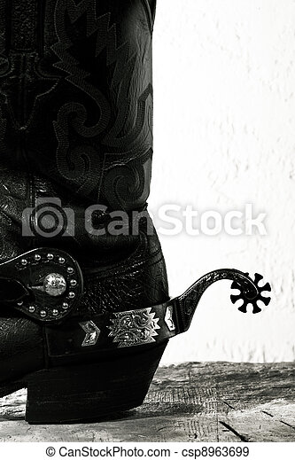 Old-fashioned western still life with old cowboy shoes ans spurs - csp8963699
