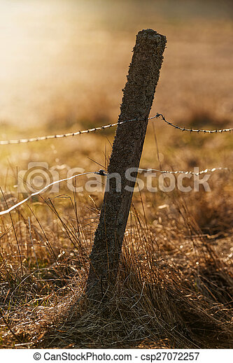 Old fence pole with barbed and electrical wire for livestock during sunset over a pasture - csp27072257
