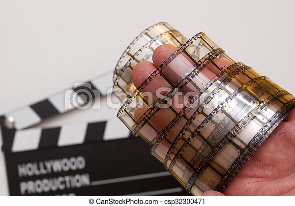 Old film strip in the man's hand - csp32300471