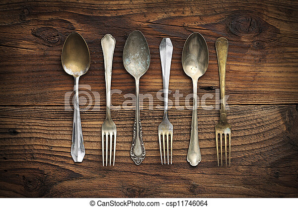 Old forks and spoons on wooden background - csp11746064