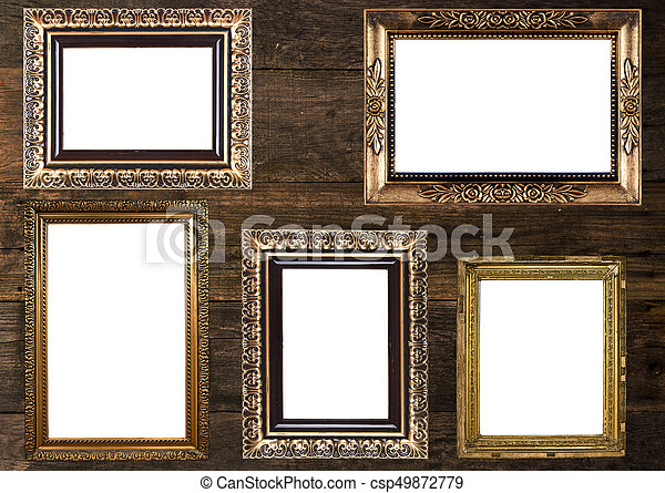 Group of old gold picture frames on wooden wall.