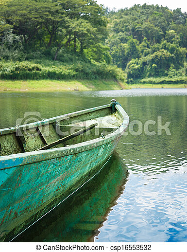 Old green iron boat in lake. - csp16553532