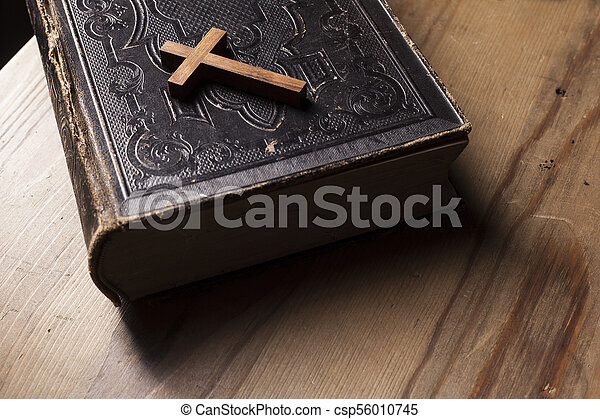 Old holy bible with wooden Christian cross - csp56010745