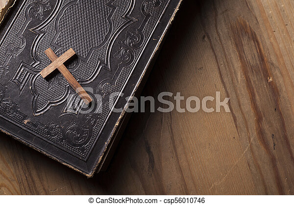 Old holy bible with wooden Christian cross - csp56010746