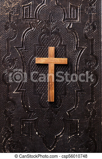 Old holy bible with wooden Christian cross - csp56010748