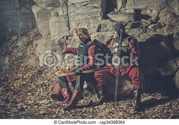 Old knight with the sword and his squire - csp34398364