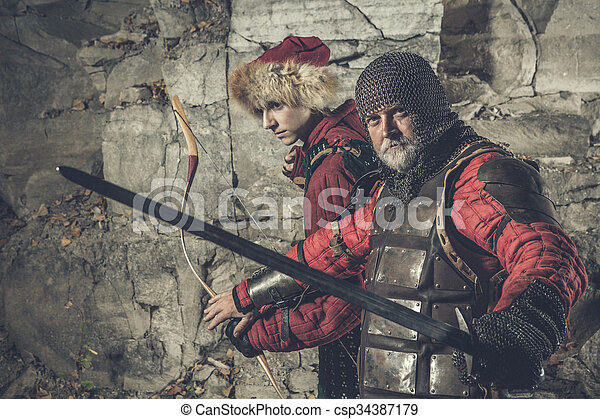 Old knight with the sword is protecting his squire - csp34387179