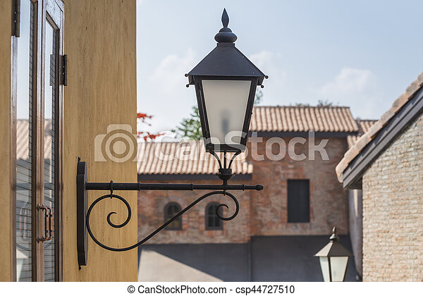old lamp on the wall with vintage building background - csp44727510