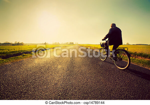 Old man riding a bike to sunny sunset sky - csp14789144
