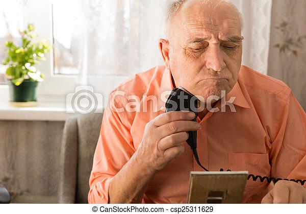 Old Man Shaving Beard with Electric Razor - csp25311629