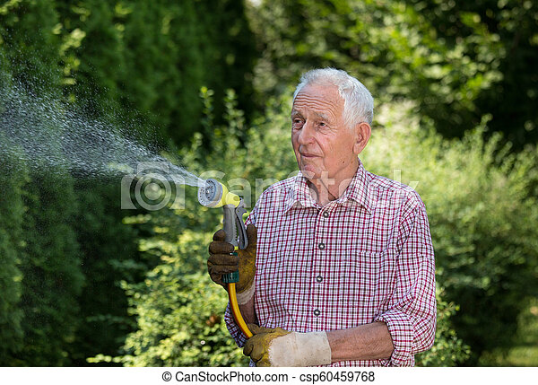 Old Man Watering Plants In Garden Senior Man Watering Plants In