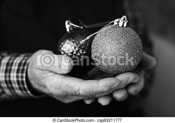 old man with some christmas balls in his hands - csp63211777