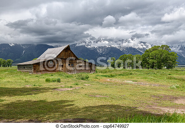 Old mormon barn in Grand Teton Mountains with low clouds. Grand Teton National Park, Wyoming, USA. - csp64749927