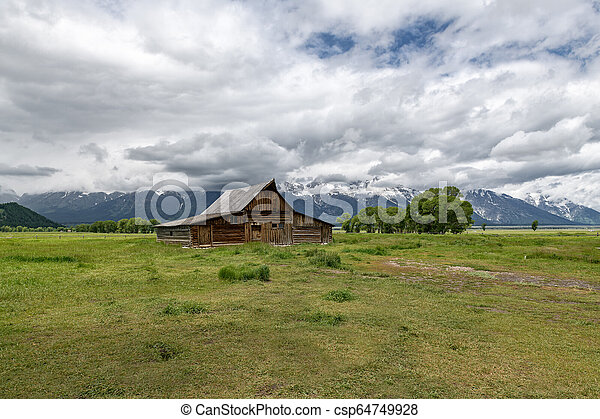 Old mormon barn in Grand Teton Mountains with low clouds. Grand Teton National Park, Wyoming, USA. - csp64749928