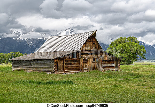 Old mormon barn in Grand Teton Mountains with low clouds. Grand Teton National Park, Wyoming, USA. - csp64749935