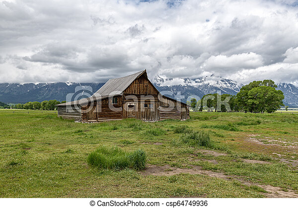 Old mormon barn in Grand Teton Mountains with low clouds. Grand Teton National Park, Wyoming, USA. - csp64749936