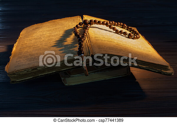 Old open bible with rosary beads. - csp77441389