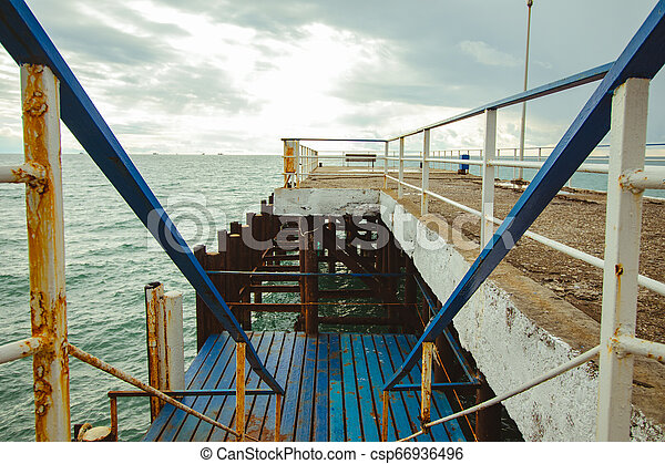 Old pier by the Black Sea on cloudy background - csp66936496