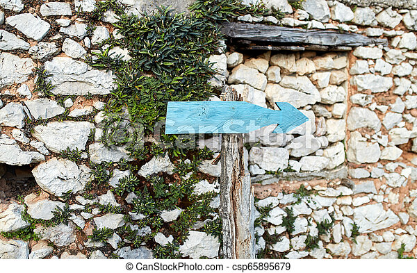 old pointer to the right on a background of a stone wall - csp65895679