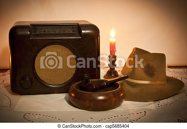 Old radio, hat, pipe and ashtray by candle light on table - csp5685404