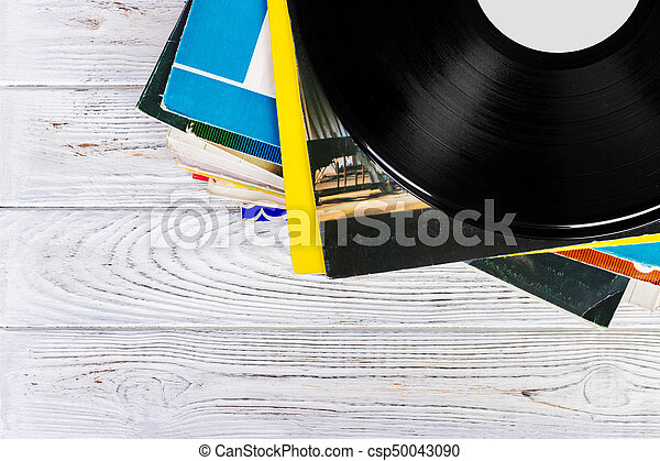 old records stack. vintage on wooden background - csp50043090