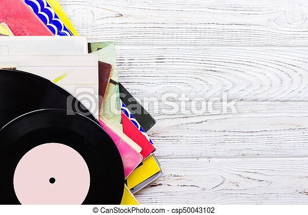 old records stack. vintage on wooden background - csp50043102