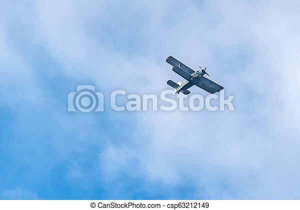Old retro plane flies in the sky - csp63212149