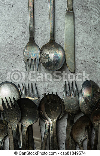 Old rustic style forks and spoons on grunge gray background - csp81849574