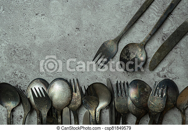 Old rustic style forks and spoons on grunge gray background - csp81849579