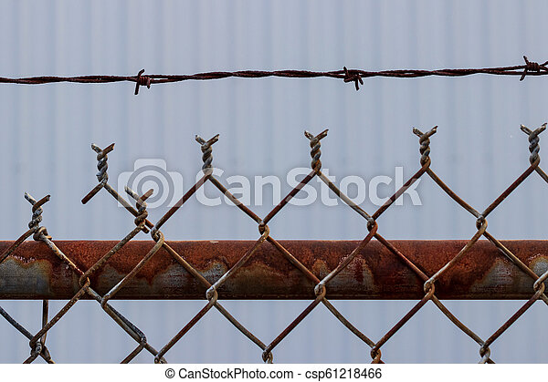 Old Rusty Chain Link Barbed Wire Fence With White Wall