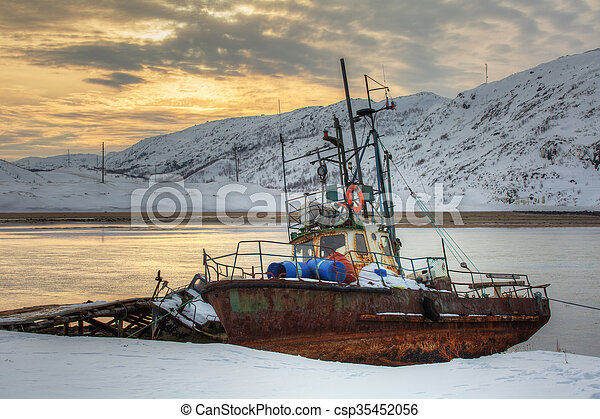 Old rusty fishing boat on the bay at sunset in winter - csp35452056