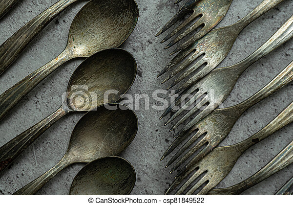 Old rusty forks and spoons on grunge gray background - csp81849522