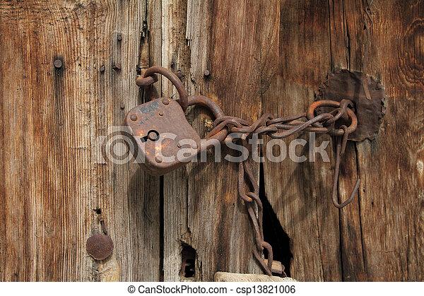 Old rusty padlock with chain on wooden door - csp13821006