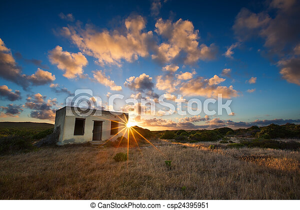 Old small deserted house in field with cloud sunset landscape - csp24395951