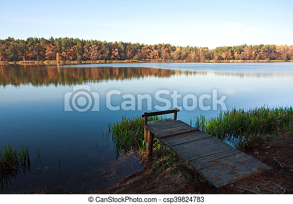 Old small wooden pier for fishing in autumn forest lake - csp39824783