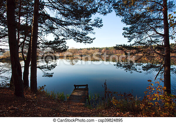 Old small wooden pier for fishing in autumn forest lake - csp39824895