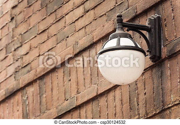 Old street lamp against a brick wall with vintage color - csp30124532