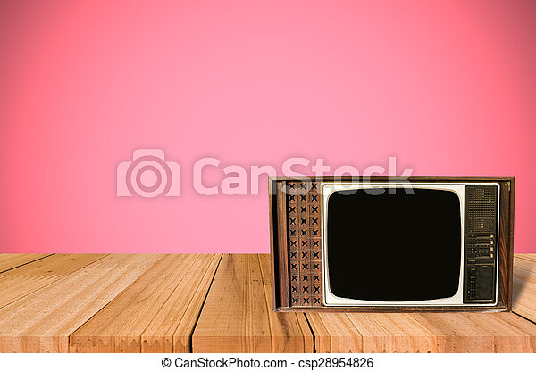 Old Style Photo. Classic vintage and retro TV on the table with pink wall background - csp28954826