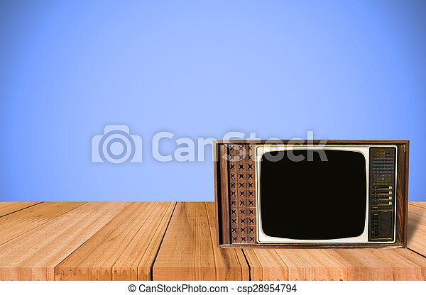 Old Style Photo. Classic vintage and retro TV on the table with blue wall background - csp28954794