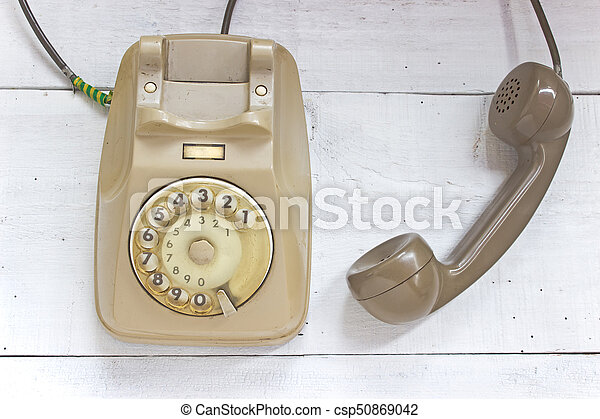 Old telephone on white wooden background - csp50869042